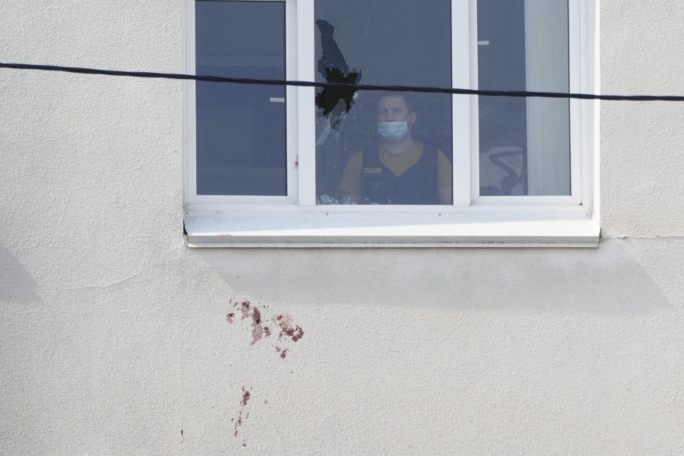 A police investigator looks at a window with a bullet hole in the school No.175 in Kazan, Russia, Wednesday, May 12, 2021, after a shooting on Tuesday. Russian officials say a gunman attacked a school in the city of Kazan and Russian officials say several people have been killed. Officials said the dead in Tuesday's shooting include students, a teacher and a school worker. Authorities also say over 20 others have been hospitalised with wounds. (AP Photo/Dmitri Lovetsky)