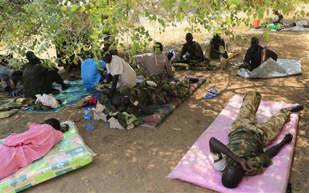 Wounded South Sudan military personnel receive medical treatment under a tree at the general military hospital compound in the capital Juba