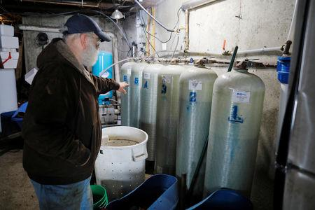 Dairy farmer Fred Stone points to the water filtration system he installed after discovering the soil, hay, and the milk from the cows contain extremely high levels of PFAS chemicals resulting from a 1980's state program to fertilize the pastures with treated sludge waste and making the milk unsuitable for sale, at the Stoneridge Farm in Arundel, Maine, U.S., March 11, 2019.  Picture taken March 11, 2019.   REUTERS/Brian Snyder