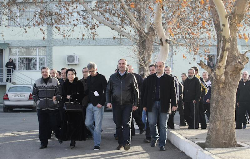 Former prisoners, accompanied by Georgian officials leave Gldani prison No. 8 in Tbilisi, Sunday, Jan. 13, 2013. Nearly 200 inmates considered political prisoners by Georgia's new parliament have walked free under an amnesty strongly opposed by President Mikhail Saakashvili. Many of those who walked free on Sunday were arrested during anti-Saakashvili protests in May 2011. Others had been convicted of trying to overthrow the government or of spying for Russia. (AP Photo) Shakh Aivazov