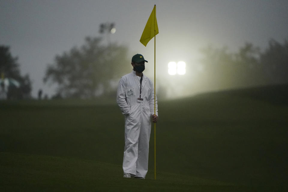 A fore caddie stands in the early morning fog during the first round of the Masters golf tournament Thursday, Nov. 12, 2020, in Augusta, Ga. (AP Photo/Chris Carlson)