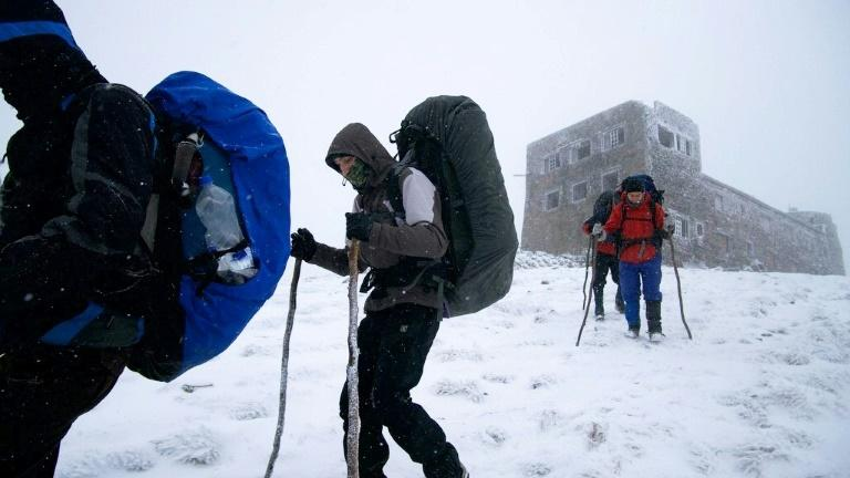 Tourists walk past Bilyi Slon, or the White Elephant, the highest inhabited building in Ukraine and an old astronomical observatory on Chornogora mountain on March 9, 2017