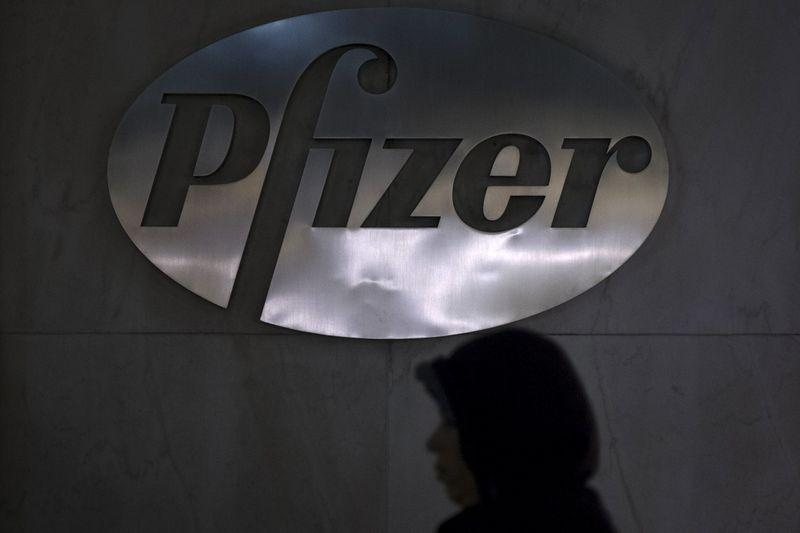 A woman walks past a Pfizer logo on their building in the Manhattan borough of New York