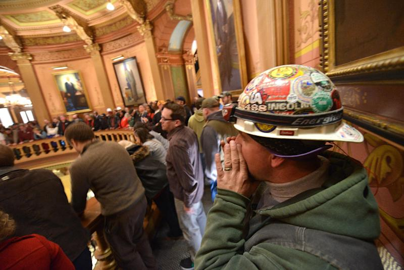 """Brett Brown or Owosso, Mich., chants as Pro-union demonstrators crowd the Rotunda in Lansing, Mich.,  to chant Wednesday afternoon Dec. 5, 2012, in the Capitol after House and Senate Democrats said there was a possibility of """"Right To Work"""" legislation coming up for a vote.     (AP Photo/Detroit News, Dale Young)  DETROIT FREE PRESS OUT; HUFFINGTON POST OUT"""