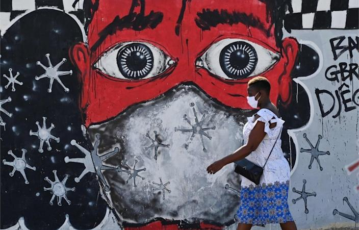 On the same day, a woman passes through a mural reminding Abidjan residents of anti-coronavirus hygiene measures ...