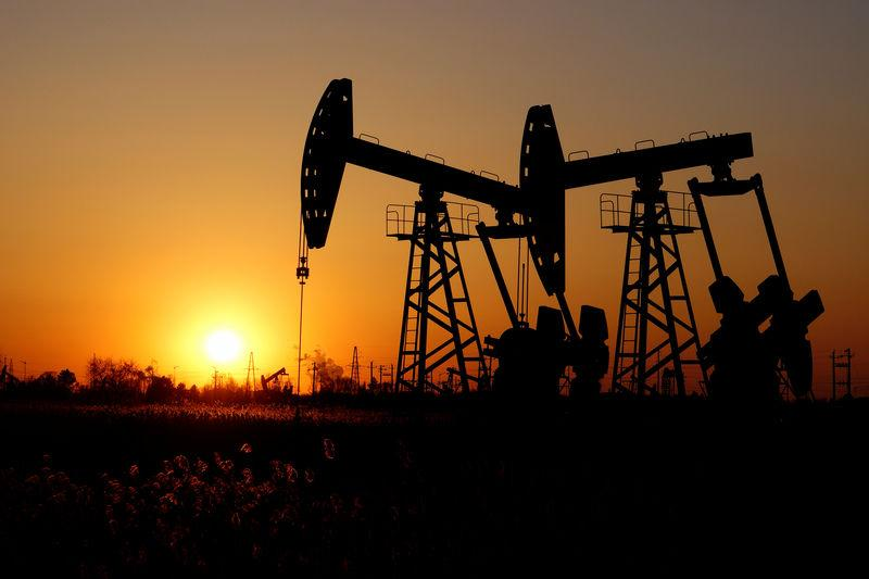 Pumpjacks are seen against the setting sun at the Daqing oil field in Heilongjiang