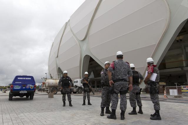 Riot police stand outside the Arena Amazonia soccer stadium three days before its scheduled inauguration, in Manaus March 6, 2014. The Arena Amazonia will host four matches of the 2014 World Cup. REUTERS/Bruno Kelly (BRAZIL - Tags: SPORT SOCCER WORLD CUP)
