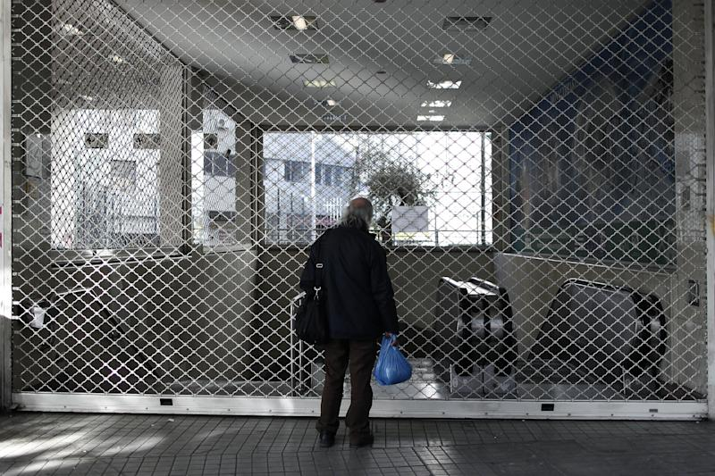 A man reads a flyer announcing a strike by metro services at the shuttered entrance of the Monastiraki Metro station in Athens, Wednesday, Jan. 23, 2013. Striking metro workers in Athens defied a court order to return to their jobs and continued their protest for a seventh day on Wednesday, as demonstrations against new pay cuts escalated in the Greek capital. (AP Photo/Petros Giannakouris)