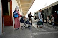 A Qatari security personnel (C) stands guard as passengers including a family bound for Germany board a shuttle bus before boarding a Qatar Airways aircraft at the airport in Kabul on September 9, 2021 (AFP/WAKIL KOHSAR)
