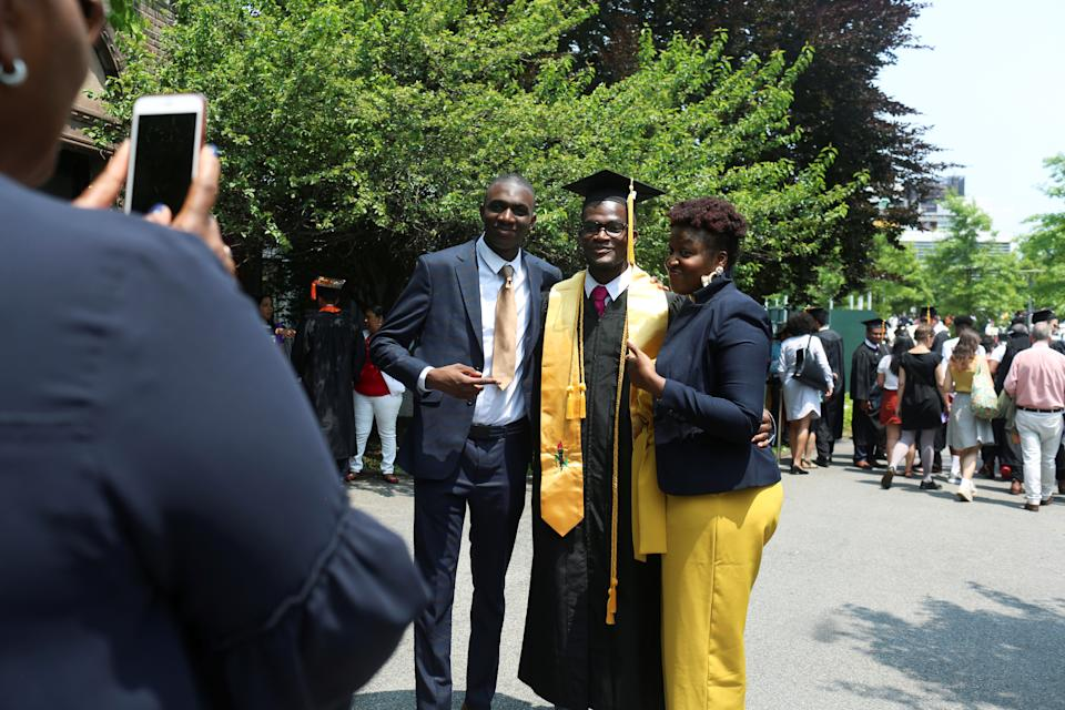 "Benjamin Philip, 23, a graduate in engineering from The City College of New York poses for photos with his family at his commencement ceremony in Manhattan on May 31, 2019. When asked about student debt he said, ""If tuition could be free, that would be best. I feel like I will be able to pay back my loans with my new job."" REUTERS/Gabriela Bhaskar"
