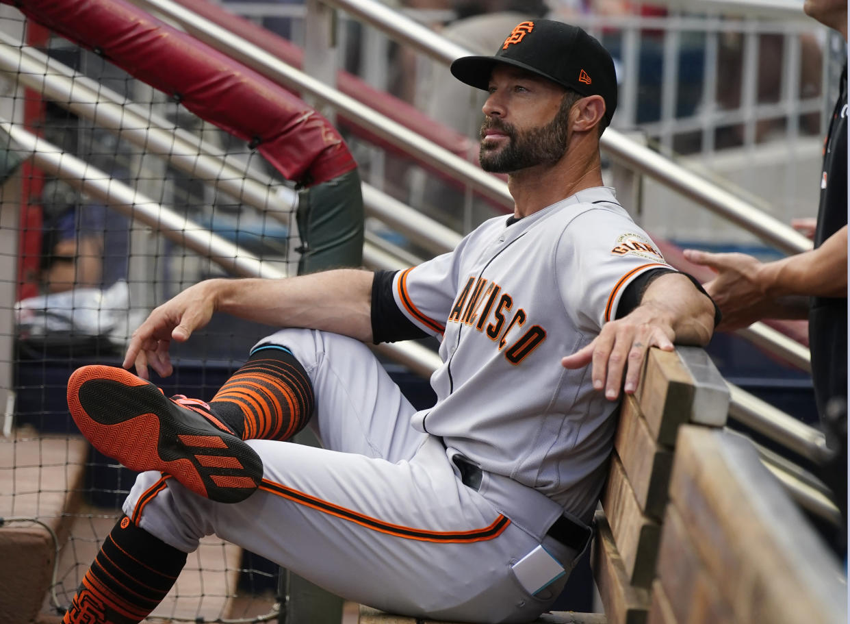 San Francisco Giants manager Gabe Kapler (19) sits on the bench as he waits for the first his team's baseball game against the Atlanta Braves to start Saturday, Aug. 28, 2021, in Atlanta. (AP Photo/John Bazemore)