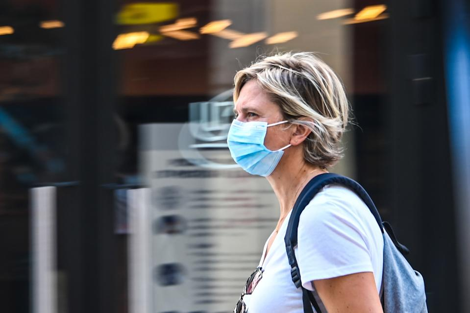 "A woman wearing a protective mask walks on a street in Lille, northern France, on July 30, 2020, as The Nord Prefecture announced, the reinforcement of the health measures at a local level to attempt to halt the rising cases of coronavirus Covid-19, which have been seen in the region during the past two weeks. - In a discussion between the French Health Minister, The Nord Prefet and Nord Regional Health Agency director (ARS) on July 29, the possibility of making the wearing of protective masks compulsory outside ""due to the proximity with Belgium"" was spoken of in an effort to halt the rise of coronavirus cases. (Photo by DENIS CHARLET / AFP) (Photo by DENIS CHARLET/AFP via Getty Images)"