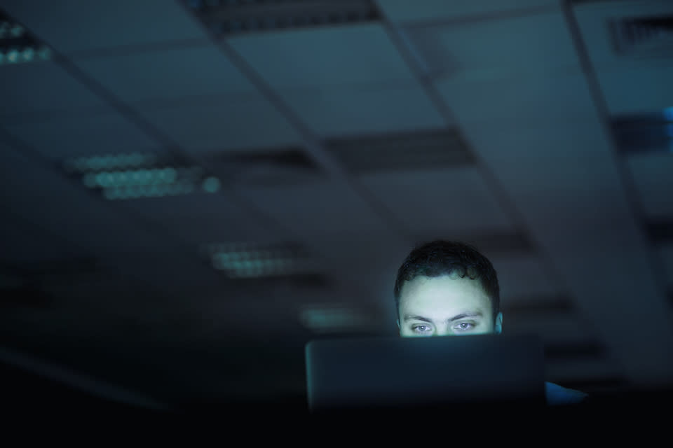 Low angle view from below of businessman man hacker identity theft thief working overtime looking on laptop computer in office space evening late night midnight alone solitude secret eyes staring glaring looking like ghost ghost like alien like sinister scary spooky security breach protocol intelligence agency government foreign steal anonymous chat bot unknown cyber warfare spam attack computer virus bug malware trojan horse power outage