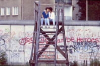 <p>Una pareja se besa subida en una escalera junto al muro que dividía la capital alemana. (Photo by Thierlein/ullstein bild via Getty Images)</p>