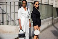 Chrissy Rutherford is seen wearing a pair of white overalls and Anna Rosa Vitiello wearing black overalls with a white bag. [Photo: Getty Images]