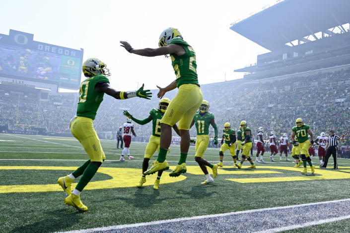 Oregon running back Travis Dye (26) celebrates his touchdown against Fresno State during the first quarter of an NCAA college football game, Saturday, Sept. 4, 2021, in Eugene, Ore. Smoke from wildfires is also seen in the stadium. (AP Photo/Andy Nelson)