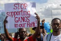 FILE - In this Dec. 10, 2020 file photo, a protester holds a sign with a message to stop supporting gangs during a protest demanding the resignation of Haitian President Jovenel Moise in Port-au-Prince, Haiti. A UNICEF report says that escalating gang violence has displaced thousands of women and children in the capital in the first two weeks of June 2021. (AP Photo/Dieu Nalio Chery, File)