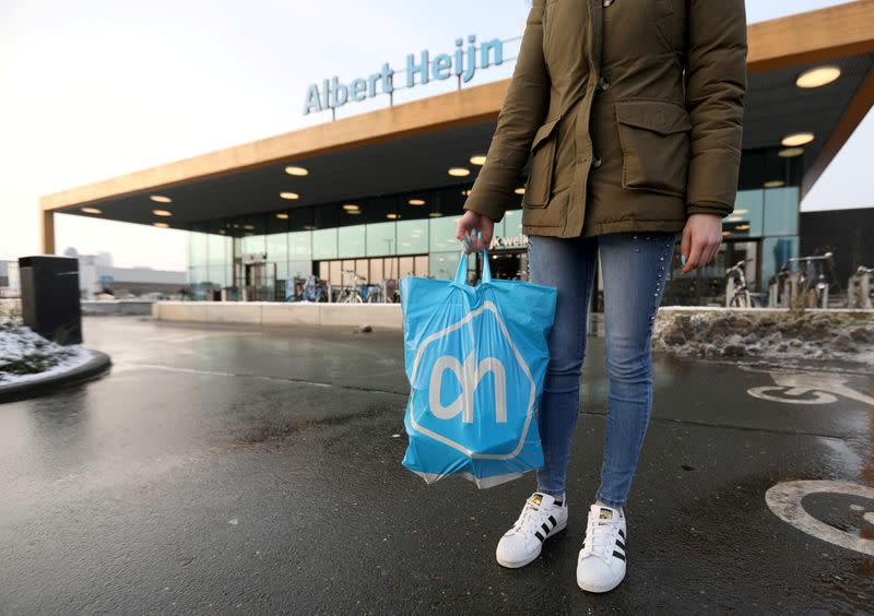 FILE PHOTO: A woman holds a bag with the logo of Albert Heijn, operated by Ahold Delhaize, the Dutch-Belgian supermarket operator, in Eindhoven