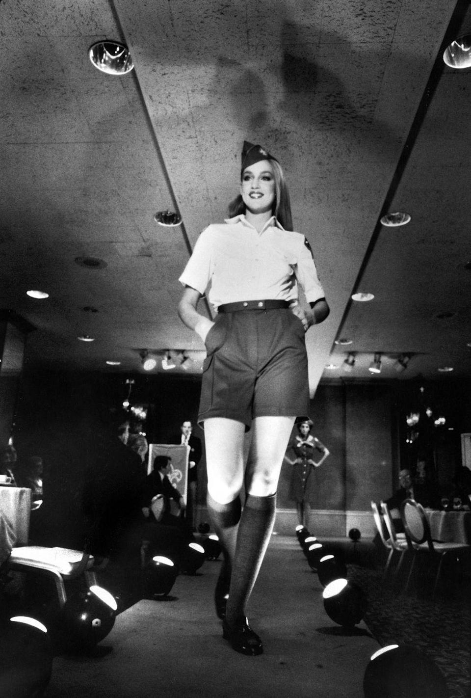 <p>Jerry Hall walks the runway in a pair of high waisted shorts in 1980. The model was dressed in a Boy Scouts-inspired outfit for an Oscar de la Renta fashion show. </p>