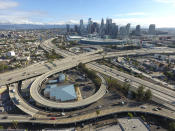 """FILE - This Friday, March 20, 2020 file photo shows the 10 Freeway and 110 Freeway with unusually light traffic during midday in downtown Los Angeles, because of the coronavirus outbreak. On Friday, March 27, 2020, The Associated Press reported on stories circulating online incorrectly asserting that Los Angeles police are doing """"spot checks"""" and ticketing people for nonessential travel during the coronavirus epidemic. Officials in Los Angeles, Los Angeles County and Santa Monica say no """"spot checks"""" are being conducted to find people violating stay-in-place orders issued to address the spread of COVID-19, and no fines have been issued. (Jeff Gritchen/The Orange County Register/SCNG via AP)"""