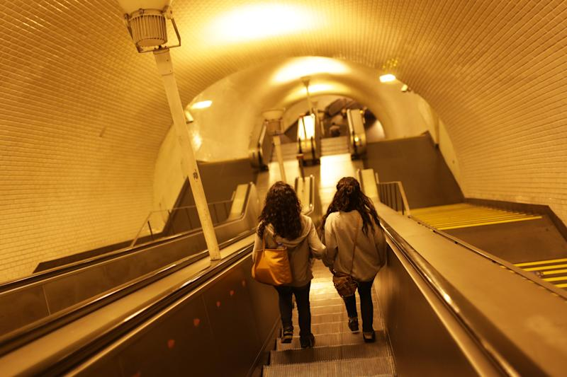 Two girls walk down the stairs of a subway station in downtown Lisbon to catch one of the last trains before the start of a 24-hour strike Monday night, Oct. 7, 2013. The capital's subway will remain closed until Thursday morning while worker's unions go on strike to protest the privatization of public transport. (AP Photo/Armando Franca)