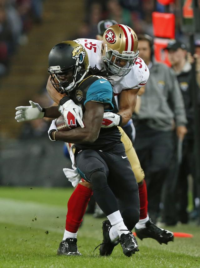 Jacksonville Jaguars running back Denard Robinson (16), is tackled by San Francisco 49ers free safety Eric Reid (35) during the NFL football game between San Francisco 49ers and Jacksonville Jaguars at Wembley Stadium in London, Sunday, Oct. 27, 2013. (AP Photo/Sang Tan)