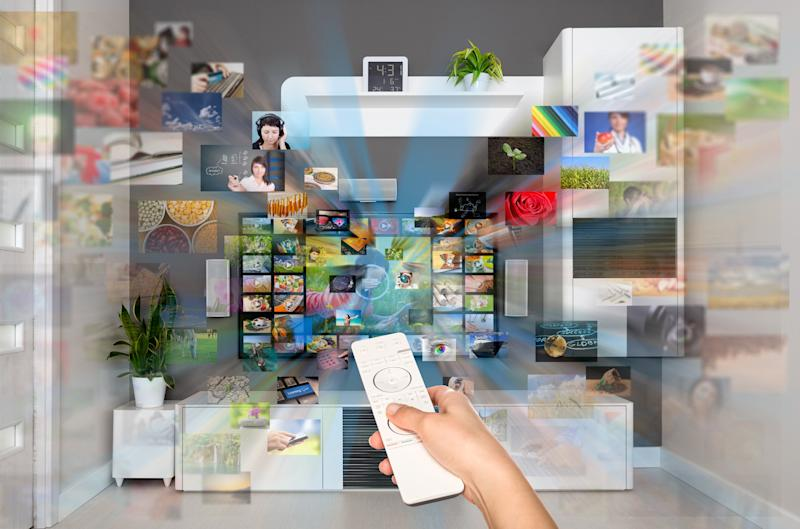 A woman's hand pointing a remote at a television as a variety of images fly towards the viewer to illustrate the vast number of viewing options.