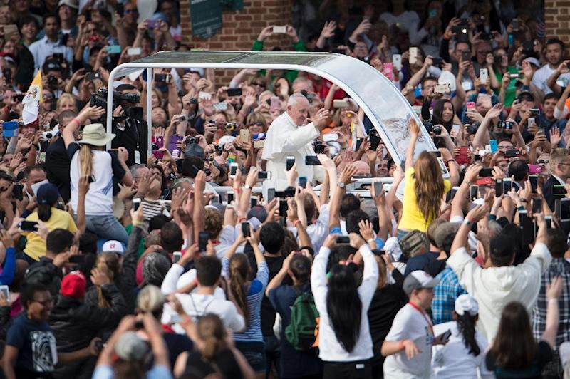 People wave as Pope Francis drives along Independence Mall on his way to Independence Hall on September 26, 2015 in Philadelphia, Pennsylvania (AFP Photo/Brendan Smialowski)