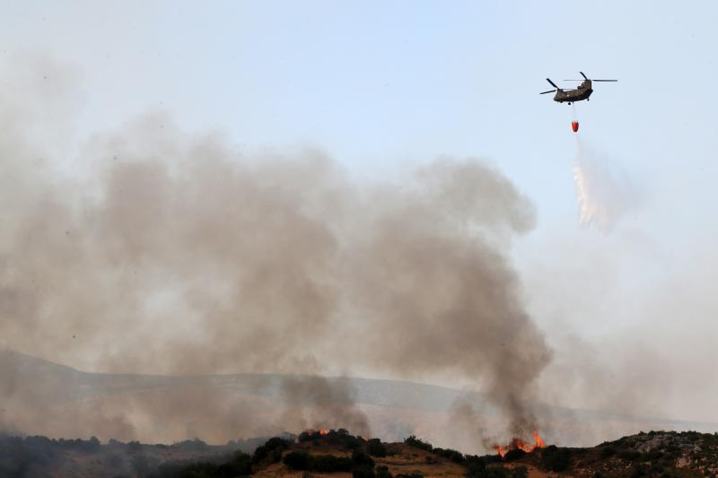 An helicopter drops water over a fire near the village of Trachyli, on the Greek island of Evia, Friday, July 5, 2019. More than 250 firefighters were battling four wildfires on the Greek island of Evia on Friday, with authorities ordering the evacuation of four villages as a precaution. (AP Photo/Thanassis Stavrakis)