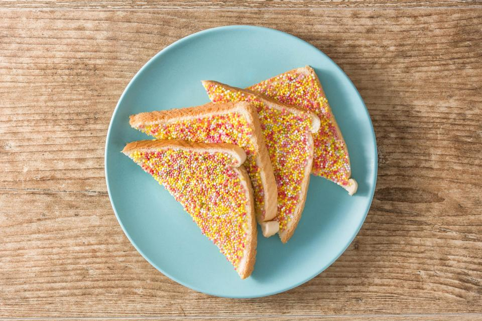 So what exactly is fairy bread? Well, here's the big reveal: it's white bread sliced into triangles, spread with butter and topped with rainbow sprinkles. That's it.