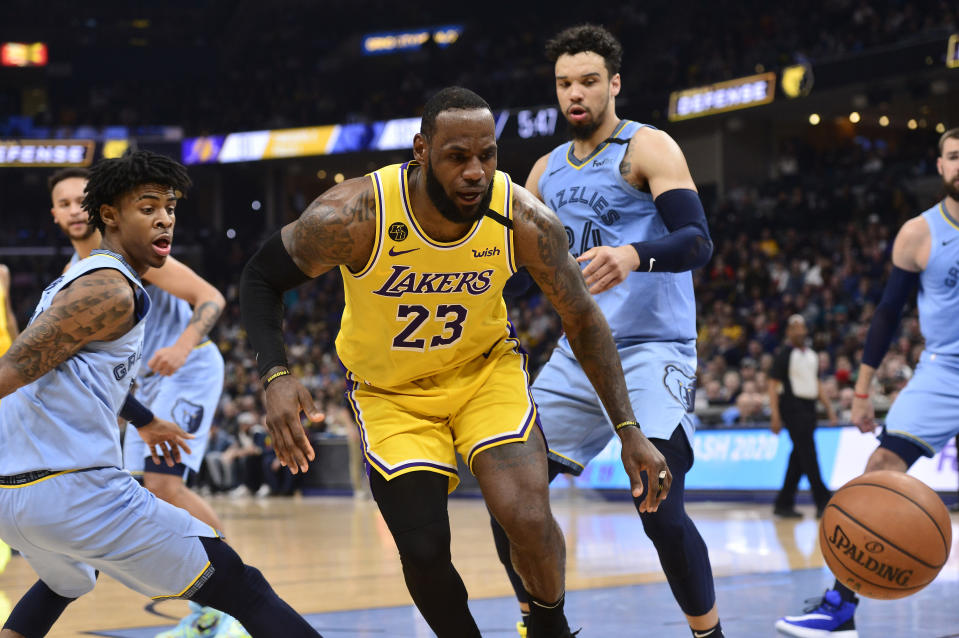Los Angeles Lakers forward LeBron James (23) loses control of the ball between Memphis Grizzlies guards Ja Morant, left, and Dillon Brooks (24) in the second half of an NBA basketball game Saturday, Feb. 29, 2020, in Memphis, Tenn. (AP Photo/Brandon Dill)