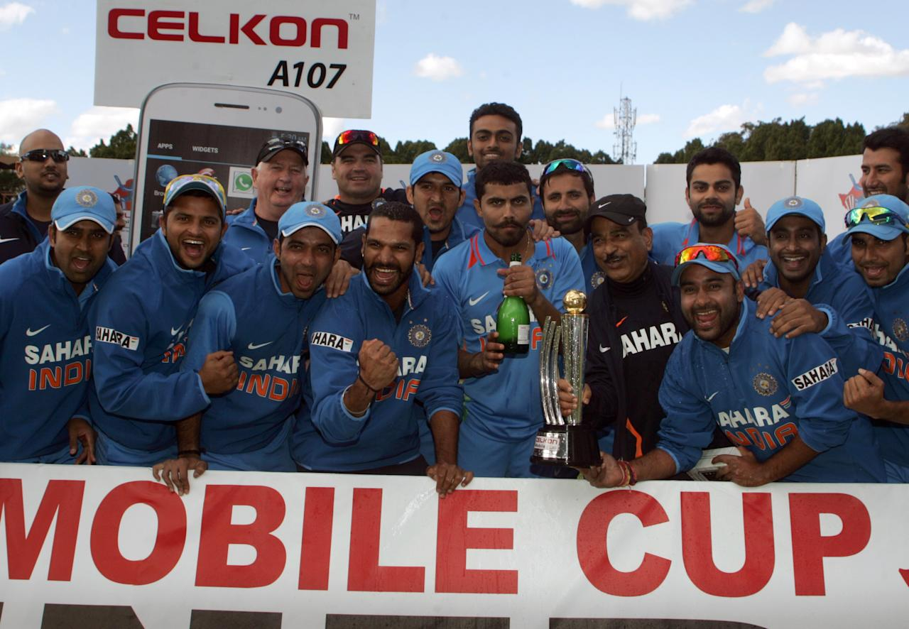 The India team celebrates with the Celkon Trophy after winning the final game of the 5 match cricket ODI series between hosts Zimbabwe and India at Queens Sports Club on August 3, 2013. AFP PHOTO /Jekesai Njikizana.        (Photo credit should read JEKESAI NJIKIZANA/AFP/Getty Images)