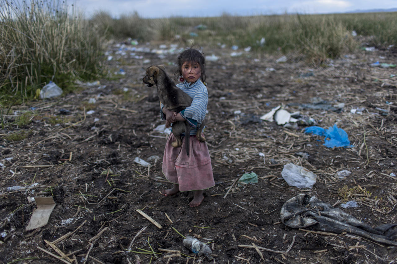 <p>Melinda Quispe walks on the trash-strewn shore of Lake Titicaca in her village of Kapi Cruz Grande, in the Puno region of Peru on Feb. 4, 2017. (Photo: Rodrigo Abd/AP) </p>