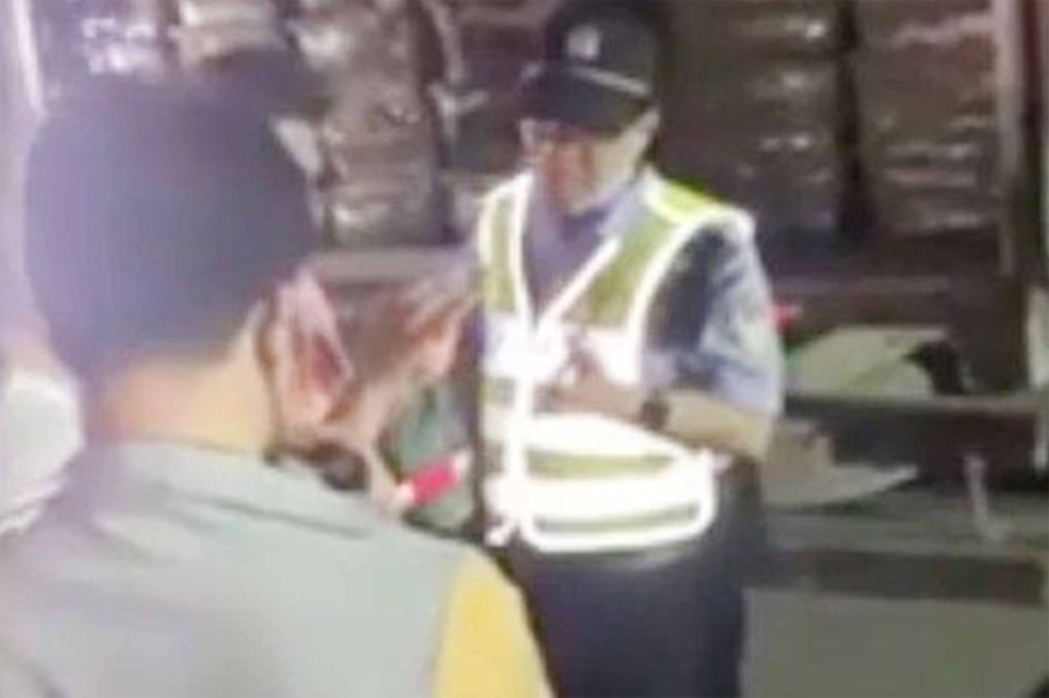 People speak with man in hi vis vest next to courier truck in China.