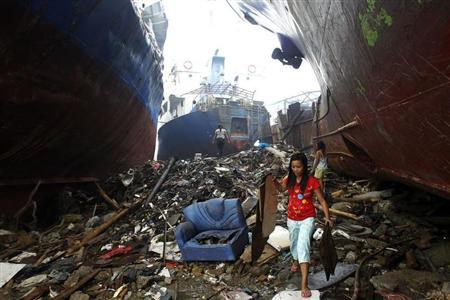 Victims of the super typhoon Haiyan pick up pieces of plywood beside cargo ships that were washed ashore by the typhoon at the battered Tacloban city