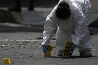 A forensic investigator tags cartridges at the scene where the Mexican capital's police chief was attacked by gunmen in Mexico City, Friday, June 26, 2020. Heavily armed gunmen attacked and wounded Omar GarcÌa Harfuch in an operation that left several dead. (AP Photo/Rebecca Blackwell)