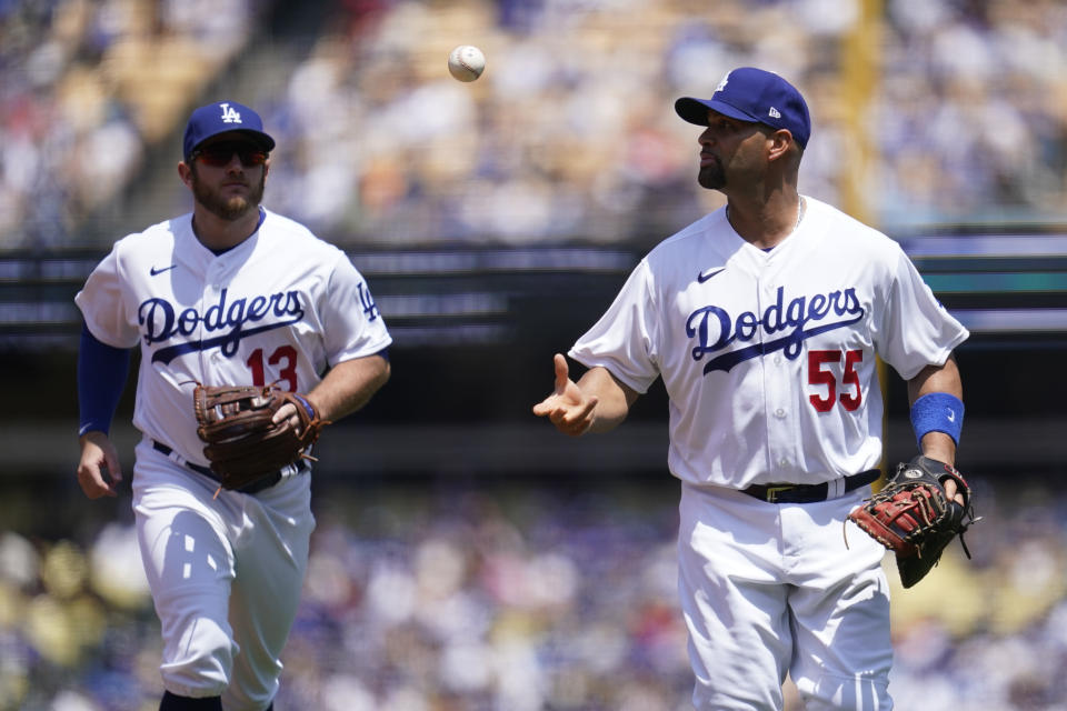 Los Angeles Dodgers first baseman Albert Pujols (55) tosses a ball to second baseman Max Muncy (13) as they run to the dugout in the middle of the third inning of a baseball game against the San Francisco Giants Sunday, May 30, 2021, in Los Angeles. (AP Photo/Ashley Landis)