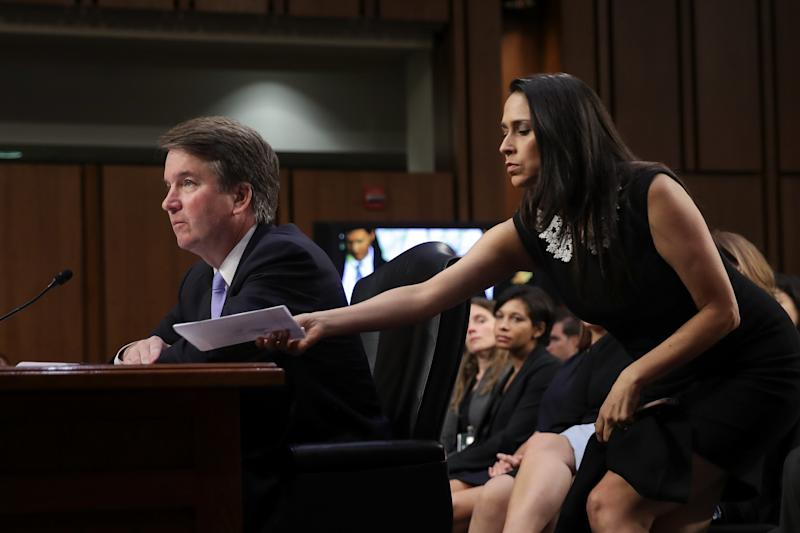Supreme Court nominee Brett Kavanaugh testifies before the Senate Judiciary Committee earlier this month as former clerk Zina Bash hands him a note. (Drew Angerer via Getty Images)
