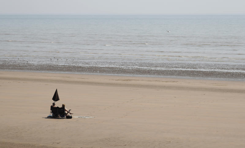 Two sunbathers sit and watch the sea on the sandy beach at Camber Sands, England, Thursday, July 25, 2019. Paris, London and places across Europe are sweltering under all-time high temperatures or near-record heat Thursday as the second heat wave this summer bakes the continent. (AP Photo/Alastair Grant)