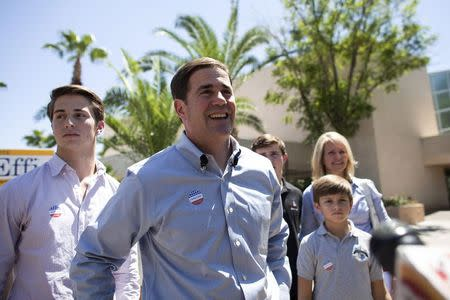 Arizona Republican gubernatorial primary candidate Doug Ducey smiles after voting, as he stands alongside his family, in the Paradise Valley section of Phoenix, Arizona August 26, 2014. REUTERS/Samantha Sais