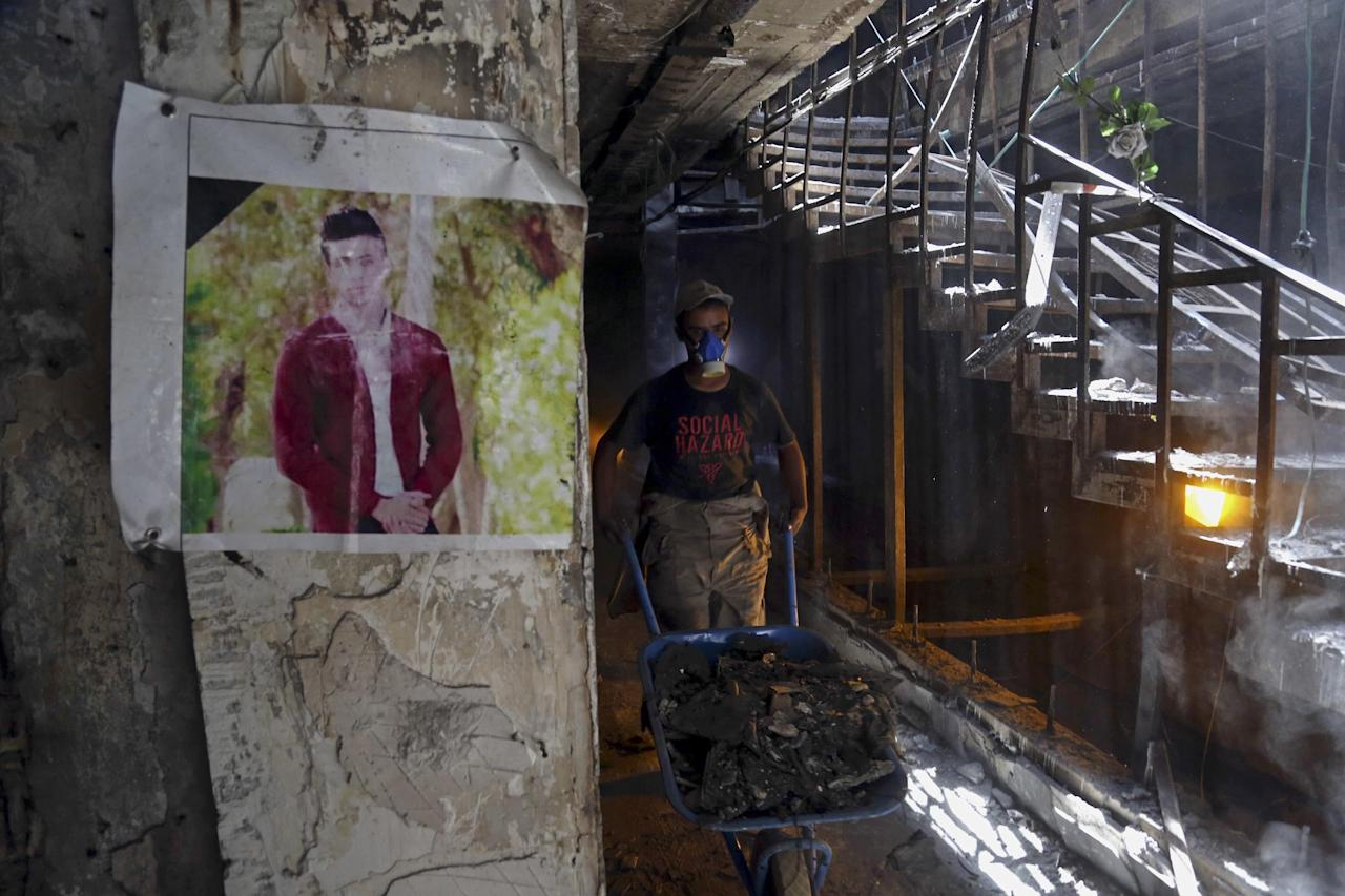 A municipal worker passes by a poster of a bomb victim during the cleaning process at the site of a deadly Islamic State group-claimed mall bombing in the Karradah neighborhood of central Baghdad, Iraq, Sunday, Aug. 21, 2016. The scene of the blast that ultimately claimed the lives of nearly 300 people, according to the ministry of health, sat as a memorial to the dead for weeks after the attack. The July 3 attack was the single deadliest bombing in Baghdad since the 2003 toppling of Saddam Hussein and it fueled anger toward the Iraqi government over the lack of security in the capital. (AP Photo/ Khalid Mohammed)