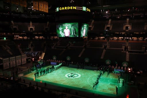 The Boston Celtics and the Milwaukee Bucks observe a moment of silence in memory of former Celtic Tommy Heinsohn, who died in November, before an NBA basketball game, Wednesday, Dec. 23, 2020, in Boston. (AP Photo/Michael Dwyer)