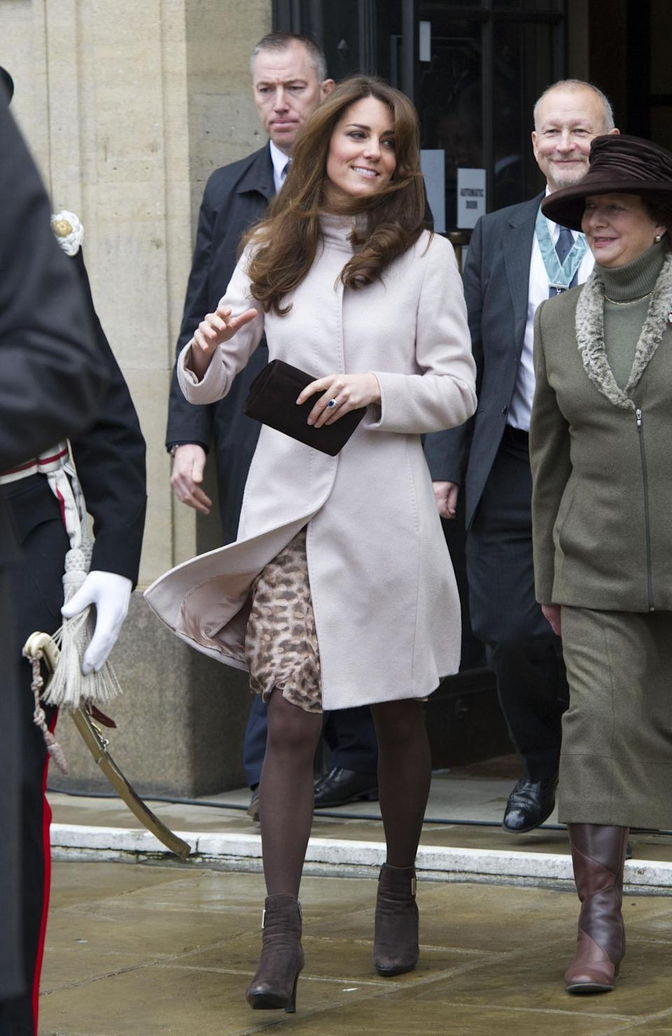 <p>For a trip to Cambridge, Kate donned a beige belted coat by Max Mara with a printed dress underneath. She accessorised with brown suede ankle boots by favourite label, Aquatalia. </p><p><i>[Photo: PA]</i></p>