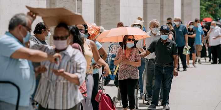 New Yorkers in need wait in a long line to receive free produce, dry goods, and meat at a Food Bank For New York City distribution event at Lincoln Center on July 29, 2020 in New York City.