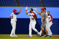 Dominican Republic's Jose Bautista, center, celebrate with teammates after hitting the game winning RBI single during the ninth inning of a baseball game against Israel at the 2020 Summer Olympics, Tuesday, Aug. 3, 2021, in Yokohama, Japan. The Dominican Republic won 7-6. (AP Photo/Matt Slocum)