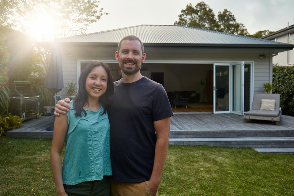 Pictured: Happy first home buyer couple in their 30s outside their house. Image: Getty