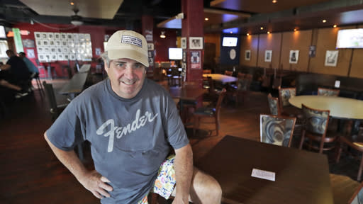 Mike Miller, owner of Wilbert's Food & Music, poses in an almost empty restaurant before a baseball game between the Minnesota Twins and the Cleveland Indians, Tuesday, Aug. 25, 2020, in Cleveland. The coronavirus pandemic has been especially hard on businesses that rely on ballpark traffic, eliminating crowds at major league games, and leading to rules that limit the amount of people they can have inside their doors at the same time.(AP Photo/Tony Dejak)