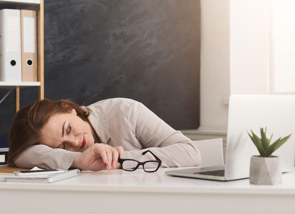 tired woman lying down on desk at work