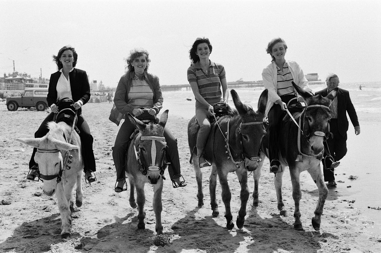 The Nolan sisters, who are appearing at the Winter Gardens, enjoy themselves riding donkeys on the sands at Blackpool. 17th July 1980. (Photo by Charles Ley/Mirrorpix via Getty Images)
