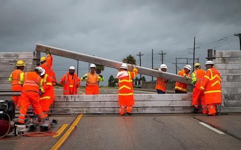TxDOT crews install the final portion of a surge wall on TX-361 leading to the Port Aransas ferry in Aransas Pass, Texas, on Friday, Aug. 25, 2017 - Credit: Nick Wagner /Austin American-Statesman via AP